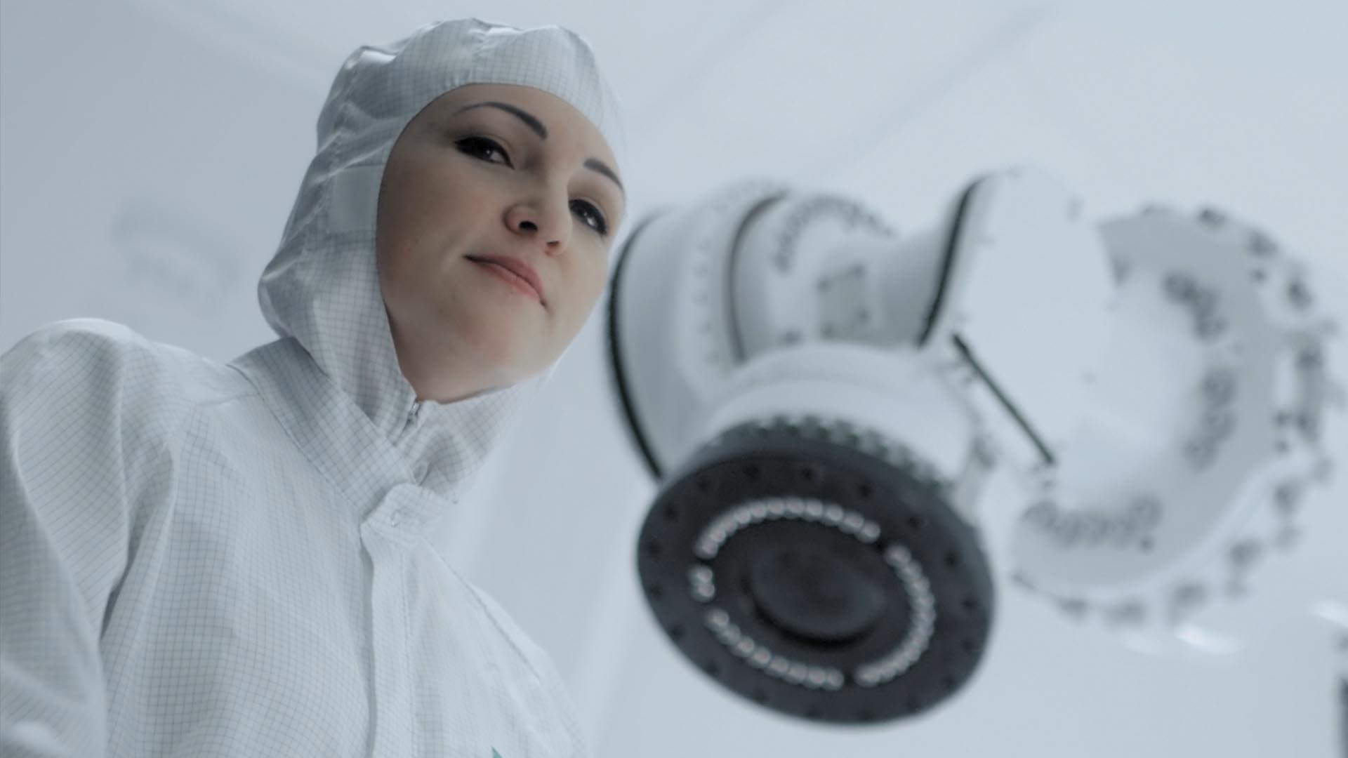 Ausschnitt aus dem Fraunhofer Recruitingspot, eine Frau in Schutzanzug steht vor einer Maschine