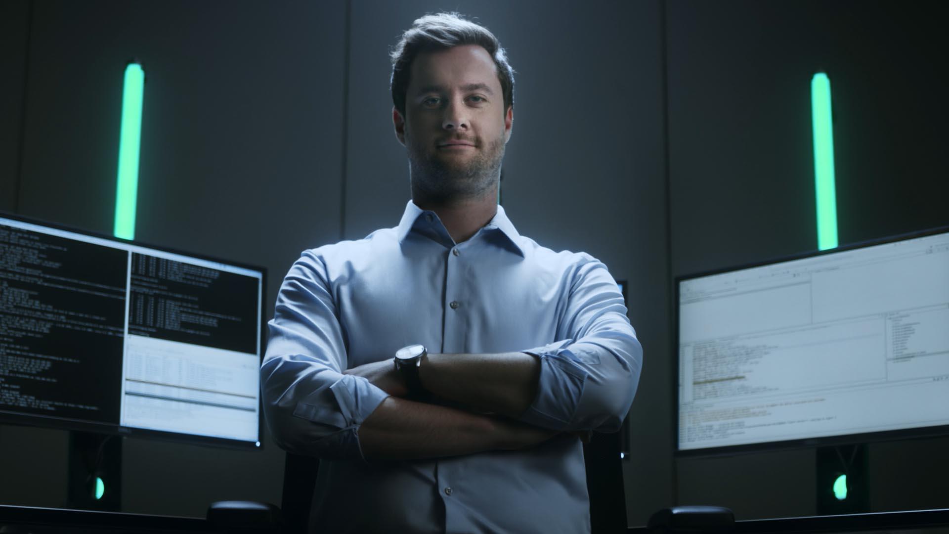Ausschnitt aus dem Fraunhofer Recruitingspot, Mann steht zufrieden vor einigen Bildschirmen welche komplexen Code anzeigen