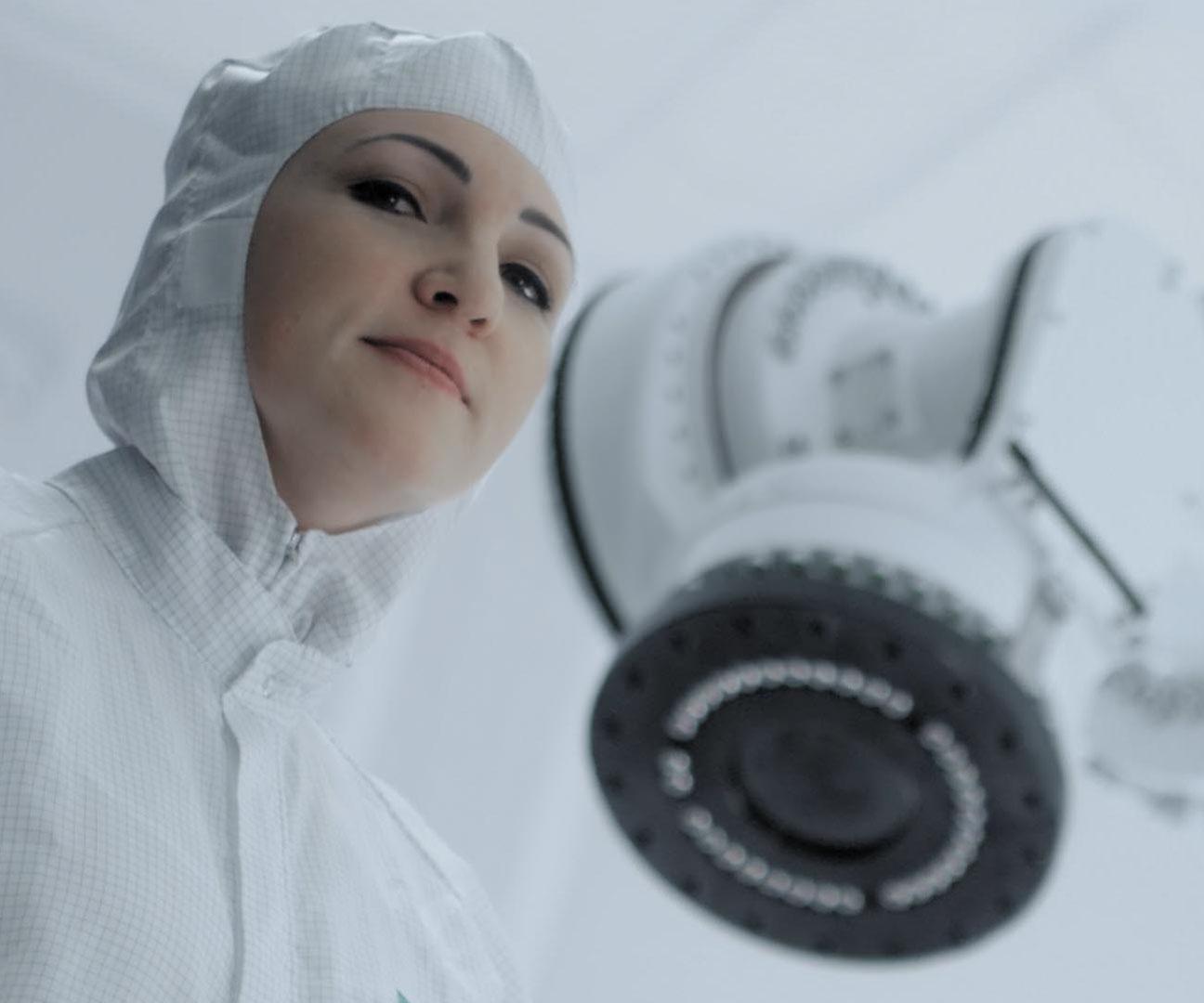 Frau in Schutzanzug vor einer Maschine