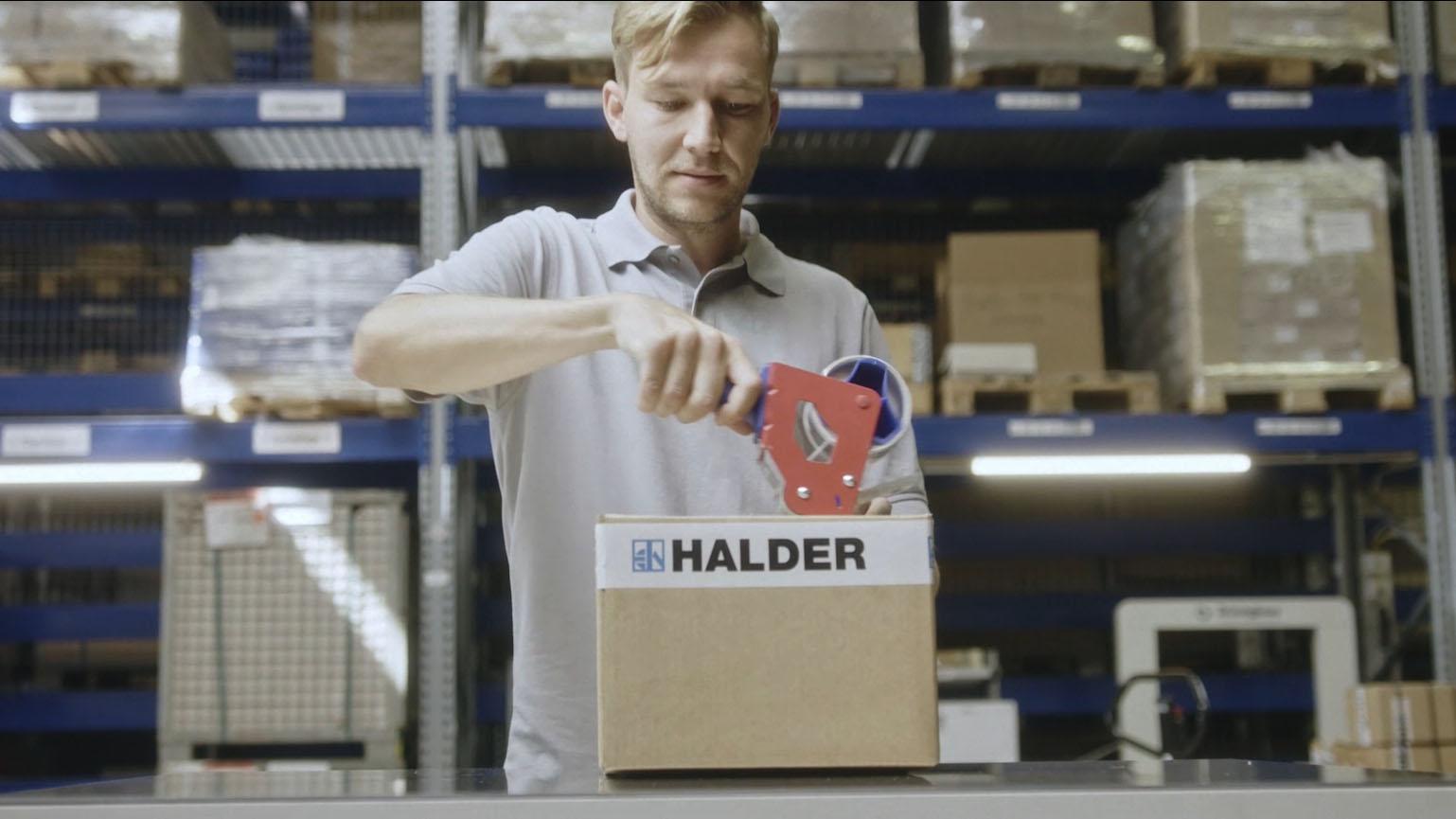 Aus dem Halder Inside Imagefilm - Mann verpackt Paket von Halder