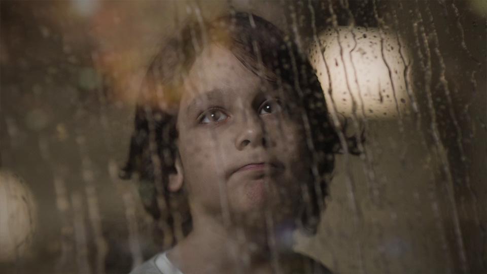 Kind traurig hinter verregnetem Fenster