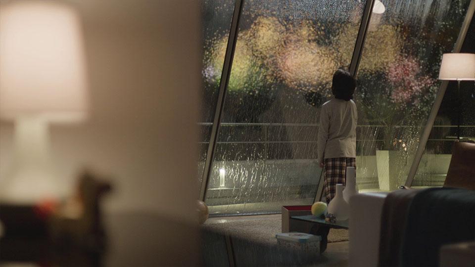 Kind vor verregnetem Fenster