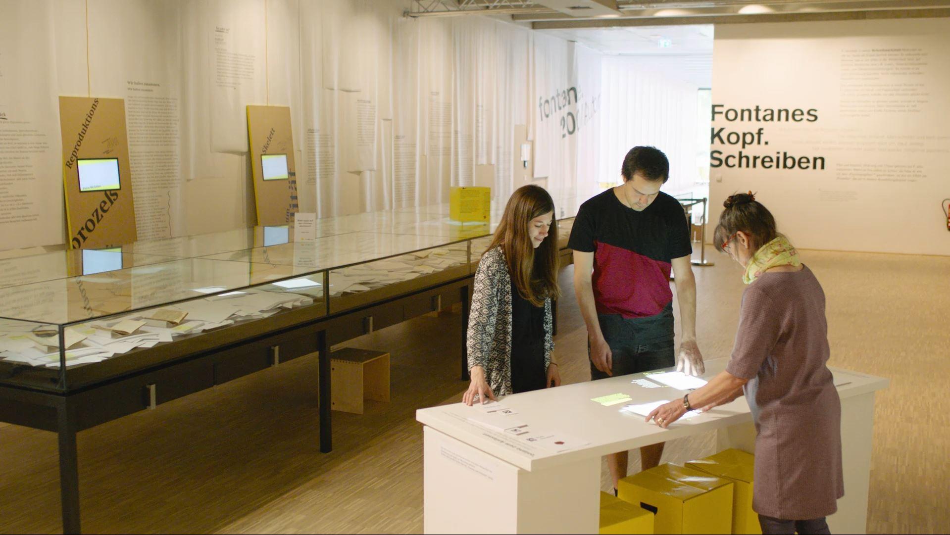 3 Personen am interaktiven Tisch entdecken Fontane