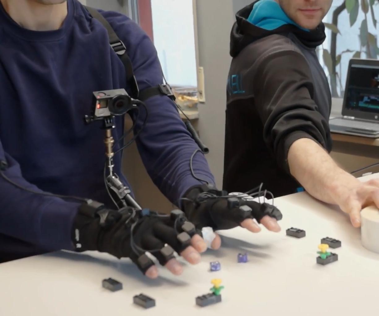 GTÜ Hands Making-Of - Hände mit Handschuh über dem Tisch
