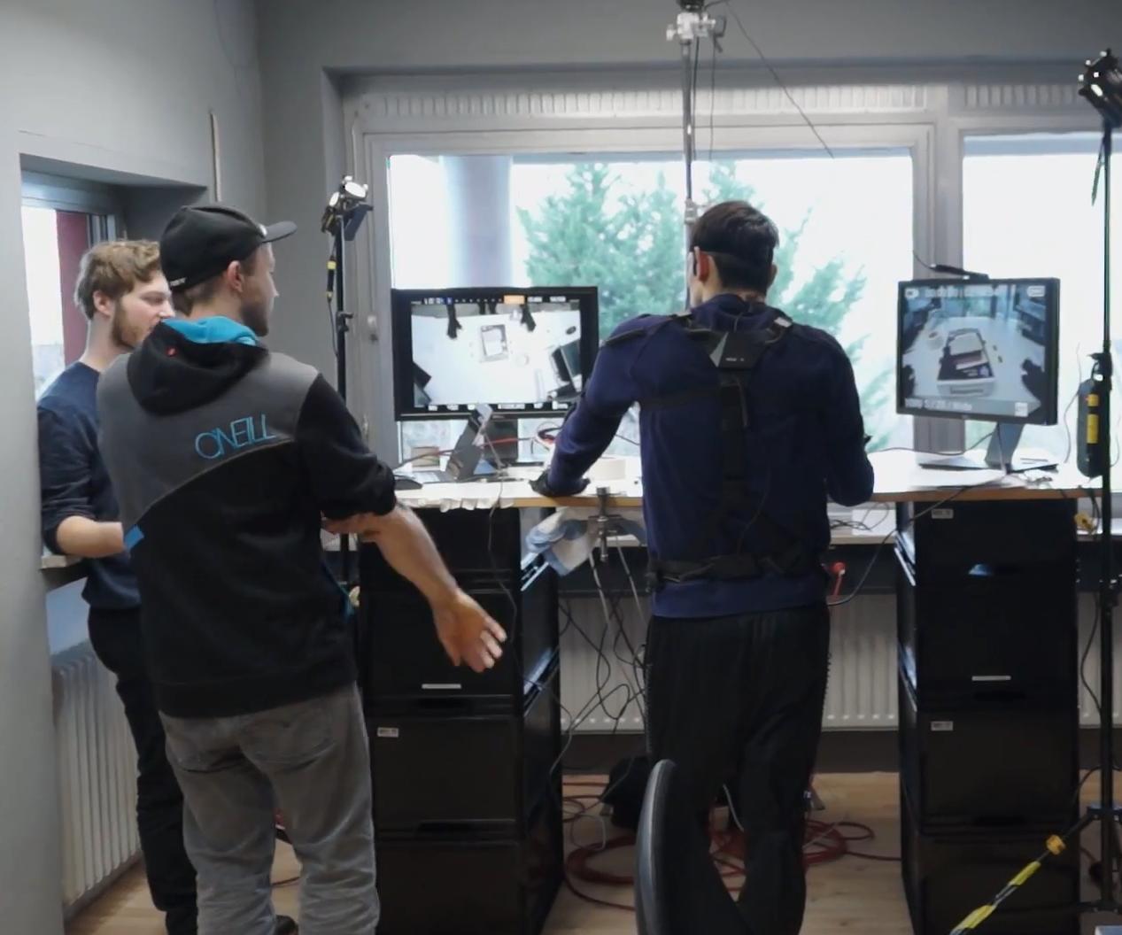 GTÜ Hands Making-Of - Aufnahme von hinten, Personen beim Motion Capture mit Displays
