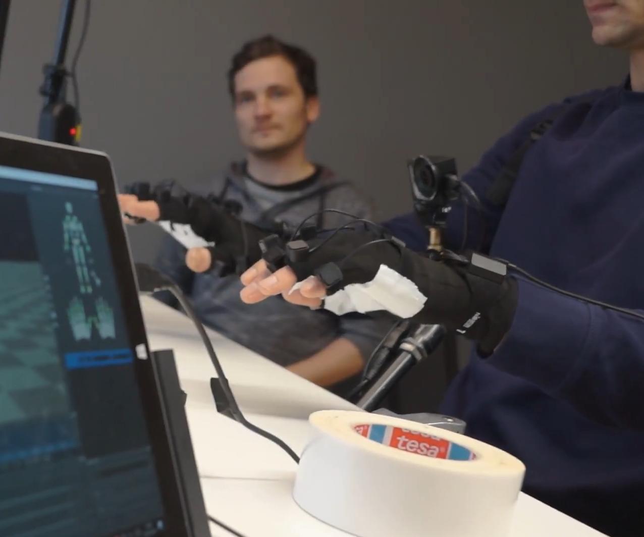 GTÜ Hands Making-Of - Hände mit Handschuhe über Tisch, Software im Vordergrund